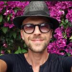 Селфи мужчина в шляпе на фоне фиолетовых цветов