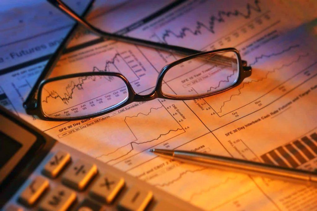 Очки лежат на столе с биржевыми графиками